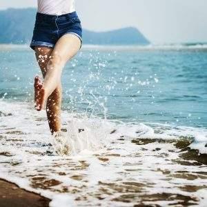 woman kicking water at beach